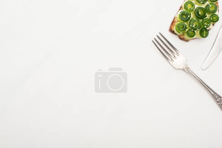 top view of fresh cucumber toast with seeds and cutlery on white background