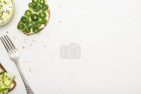 Photo for Top view of fresh cucumber toasts with seeds near yogurt in bowl and fork on white background - Royalty Free Image