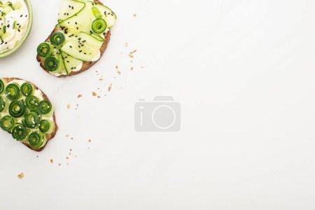 vista superior de tostadas de pepino fresco con semillas, hojas de albahaca cerca de yogur en tazón sobre fondo blanco