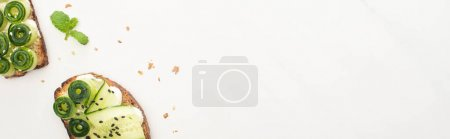 Photo for Top view of fresh cucumber toasts with seeds, mint on white background, panoramic shot - Royalty Free Image