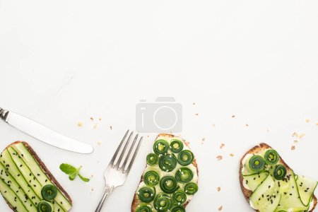 Photo for Top view of fresh cucumber toasts with seeds, mint leaves and cutlery on white background - Royalty Free Image
