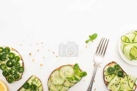 Photo for Top view of fresh cucumber toasts with seeds, mint and basil leaves and fork on white background - Royalty Free Image