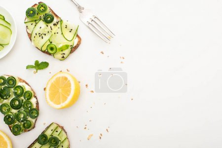 Photo for Top view of fresh cucumber toasts with seeds, mint leaves near lemon and fork on white background - Royalty Free Image