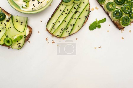 Photo for Top view of fresh cucumber toasts with seeds, mint leaves near yogurt on white background - Royalty Free Image