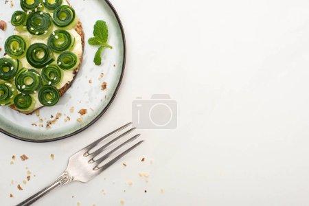 vue du dessus du pain grillé au concombre frais avec du sésame et des feuilles de menthe sur une assiette près de la fourchette sur fond blanc