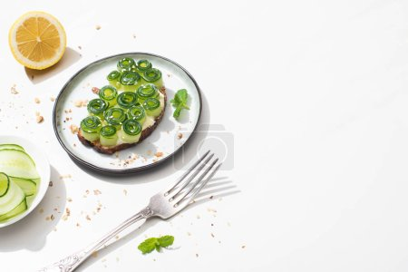 Photo for Fresh cucumber toast with sesame and mint leaves on plate near fork and lemon on white background - Royalty Free Image
