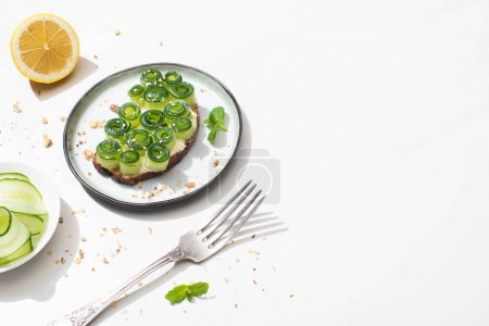 fresh cucumber toast with sesame and mint leaves on plate near fork and lemon on white background