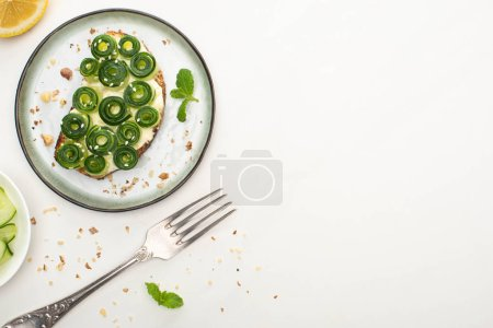 Photo for Top view of fresh cucumber toast with sesame and mint leaves on plate near fork and lemon on white background - Royalty Free Image