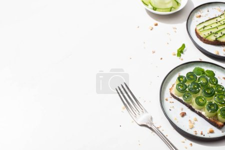 Photo for Fresh cucumber toasts on plates near fork on white background - Royalty Free Image