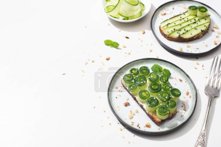 Photo pour Fresh cucumber toasts on plates near fork on white background - image libre de droit