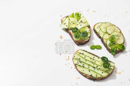 Photo pour Fresh cucumber toasts with seeds, mint and basil leaves on white background - image libre de droit