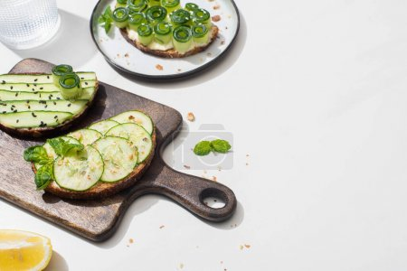 tostadas de pepino fresco sobre tabla de cortar de madera cerca del agua y limón sobre fondo blanco