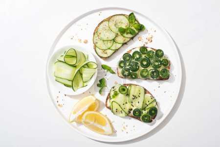 Photo for Top view of fresh cucumber toasts with seeds, mint and basil leaves on plate with lemon on white background - Royalty Free Image