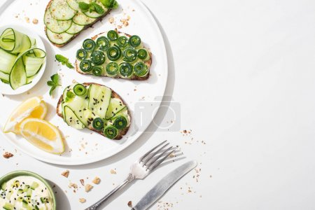 Photo for Top view of fresh cucumber toasts with seeds, mint and basil leaves on plate with lemon near cutlery and yogurt on white background - Royalty Free Image