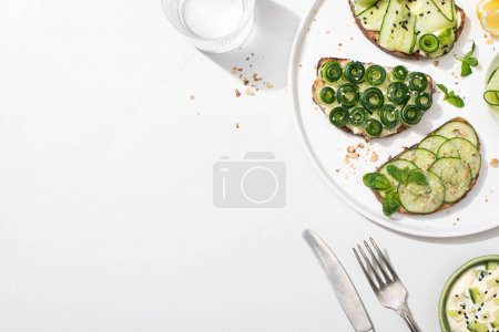 Photo for Top view of fresh cucumber toasts with seeds, mint and basil leaves on plate near cutlery, water and yogurt on white background - Royalty Free Image