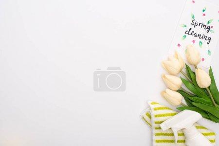 Photo pour Vue de dessus des tulipes de printemps et des fournitures de nettoyage près de la carte de nettoyage de printemps sur fond blanc - image libre de droit