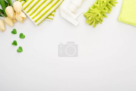 Photo for Top view of spring tulips and green cleaning supplies on white background - Royalty Free Image