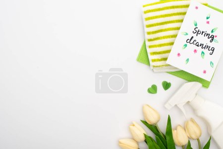 Photo for Top view of spring tulips and cleaning supplies near spring cleaning card on white background - Royalty Free Image