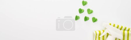 Photo for Top view of cleaning supplies and green hearts on white background, panoramic shot - Royalty Free Image