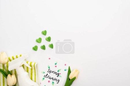 Photo pour Top view of spring tulips and green cleaning supplies near spring cleaning card on white background - image libre de droit