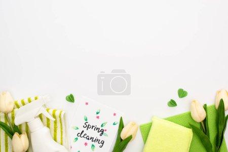 Photo pour Vue de dessus des tulipes de printemps et des fournitures de nettoyage vertes près de la carte de nettoyage de printemps sur fond blanc - image libre de droit