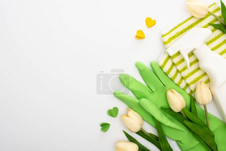 Photo for Top view of spring tulips and green cleaning supplies and hearts on white background - Royalty Free Image