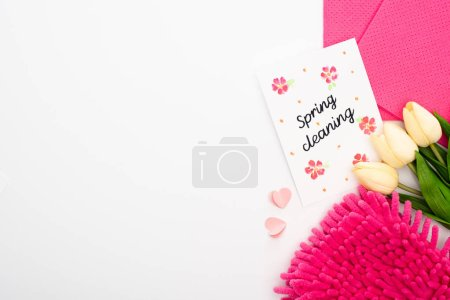 Photo for Top view of tulips and pink cleaning supplies near spring cleaning card on white background - Royalty Free Image