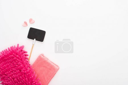 top view of pink cleaning supplies, hearts and empty sign on white background