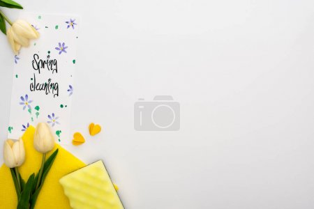 Foto de Vista superior de los tulipanes de primavera y suministros de limpieza amarilla cerca de la tarjeta de limpieza de primavera en fondo blanco. - Imagen libre de derechos