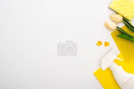 Photo pour Vue de dessus des tulipes de printemps et des fournitures de nettoyage jaunes sur fond blanc - image libre de droit