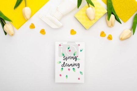 Foto de Vista superior de los tulipanes de primavera y suministros de limpieza amarillos con corazones cerca de la tarjeta de limpieza de primavera sobre fondo blanco - Imagen libre de derechos