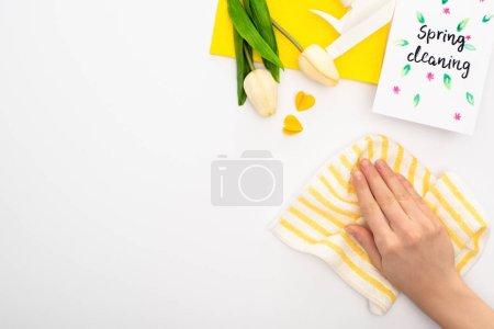 Photo pour Vue recadrée de la femme tenant le chiffon près des tulipes de printemps, fournitures de nettoyage jaune, carte de nettoyage de printemps sur fond blanc - image libre de droit