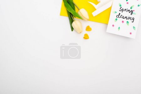 Photo for Top view of spring tulips and yellow cleaning supplies near spring cleaning card on white background - Royalty Free Image
