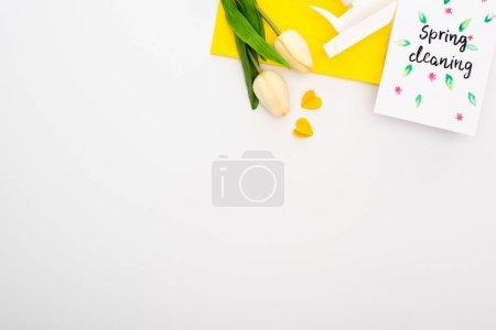 Photo pour Vue de dessus des tulipes de printemps et des fournitures de nettoyage jaunes près de la carte de nettoyage de printemps sur fond blanc - image libre de droit
