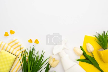 top view of spring tulips and green plants near yellow cleaning supplies and hearts on white background