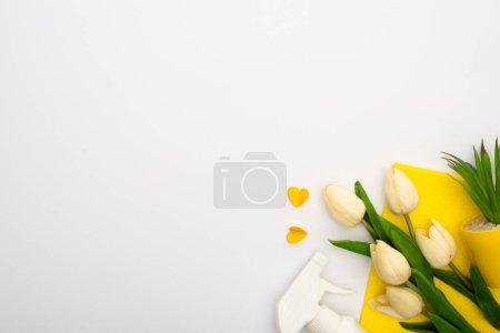 Photo pour Vue du dessus des tulipes printanières et des plantes vertes près des fournitures de nettoyage jaunes et des coeurs sur fond blanc - image libre de droit