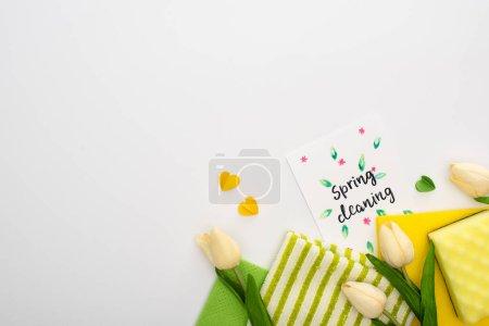 Photo pour Vue de dessus des tulipes de printemps, des fournitures de nettoyage vert et jaune avec des coeurs près de la carte de nettoyage de printemps sur fond blanc - image libre de droit