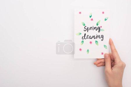 Foto de Vista recortada de la mujer que tiene una tarjeta de limpieza de primavera sobre fondo blanco - Imagen libre de derechos
