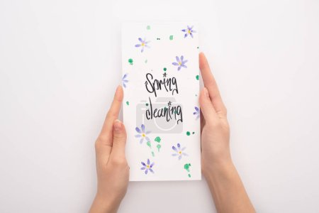 vista recortada de la mujer sosteniendo la tarjeta de limpieza de primavera sobre fondo blanco