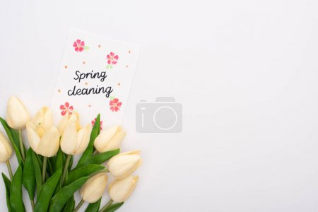 Photo pour Top view of spring tulips near spring cleaning card on white background - image libre de droit