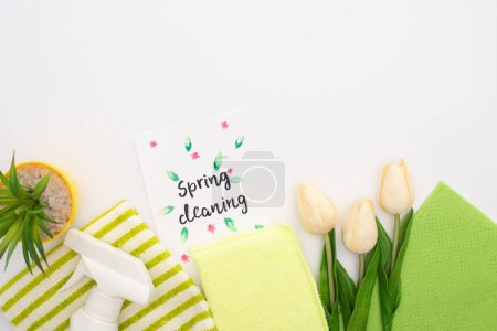 Photo for Top view of spring tulips and green plant near cleaning supplies and spring cleaning card on white background - Royalty Free Image