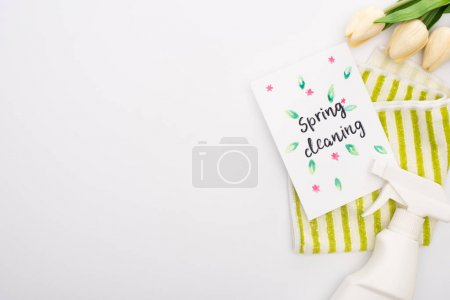Photo for Top view of spring tulips and green cleaning supplies near spring cleaning card on white background - Royalty Free Image