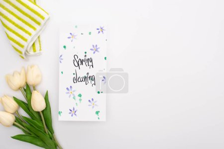 Photo for Top view of spring tulips and towel near spring cleaning card on white background - Royalty Free Image