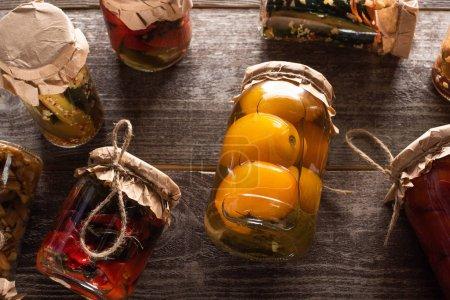 Photo pour Vue de dessus des cornichons savoureux faits maison dans des bocaux sur la table en bois - image libre de droit