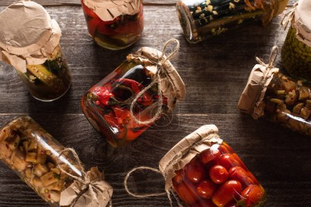 top view of homemade tasty pickles in jars on wooden table