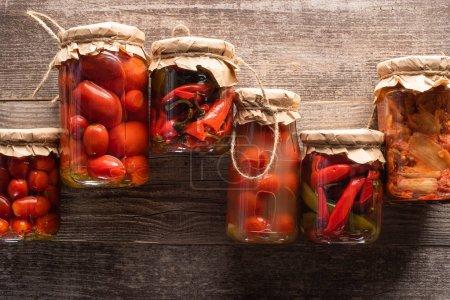Blick von oben auf rote hausgemachte leckere Essiggurken in Gläsern auf Holztisch