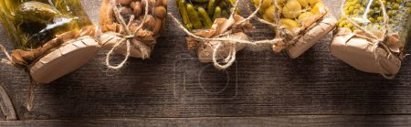 top view of homemade tasty pickles in jars on wooden table with copy space, panoramic shot