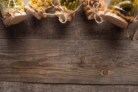 Photo pour Vue de dessus des cornichons savoureux faits maison dans des bocaux sur une table en bois avec espace de copie - image libre de droit