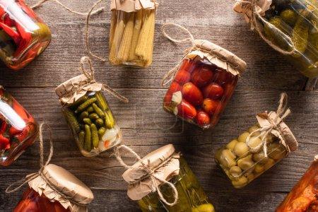 Photo pour Vue de dessus des cornichons savoureux frais faits maison dans des bocaux sur la table en bois - image libre de droit