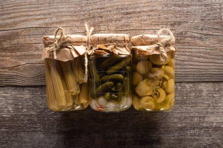 Photo pour Vue de dessus de délicieux concombres marinés maison savoureux, maïs et champignons sur table rustique en bois - image libre de droit